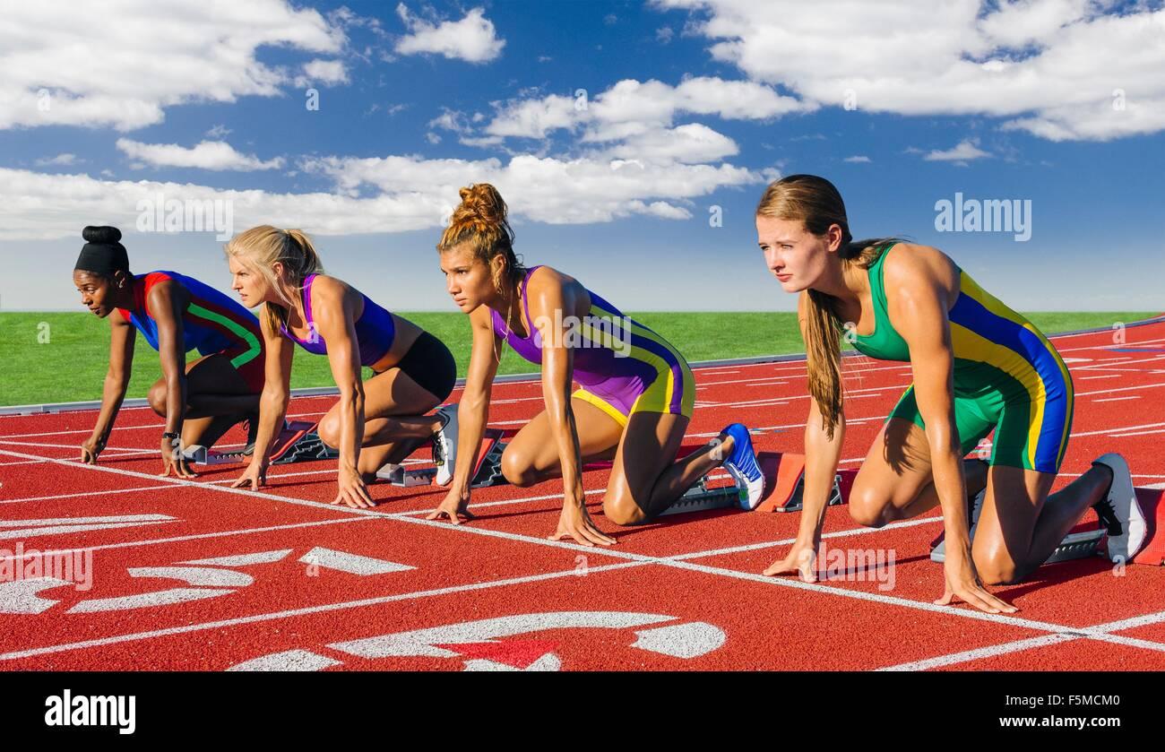 Vier weibliche Athleten auf die Leichtathletik zu verfolgen, kurz vor dem start Rennen Stockbild