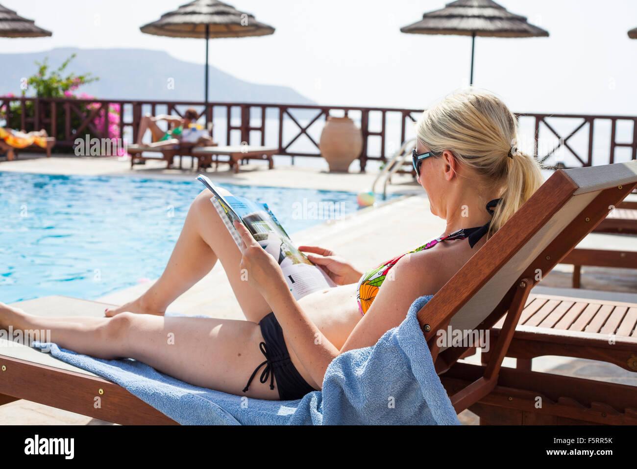 Griechenland, Karpathos Amopi, Magazin Woman lesen am pool Stockbild