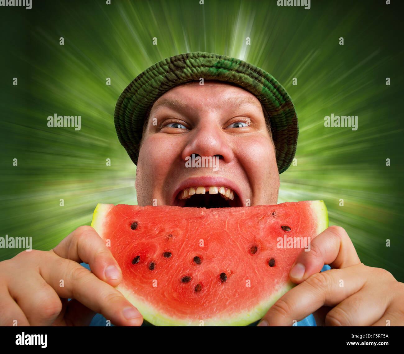 Bizarre Mann isst Wassermelone im Freien im Sommer Stockfoto