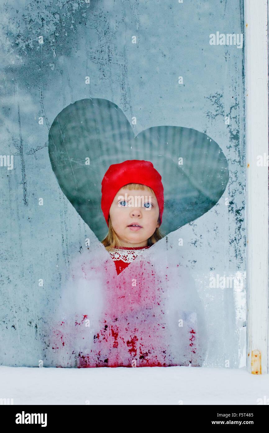 Porträt eines Mädchens (4-5) durch gefrorene Fenster schaut Stockbild