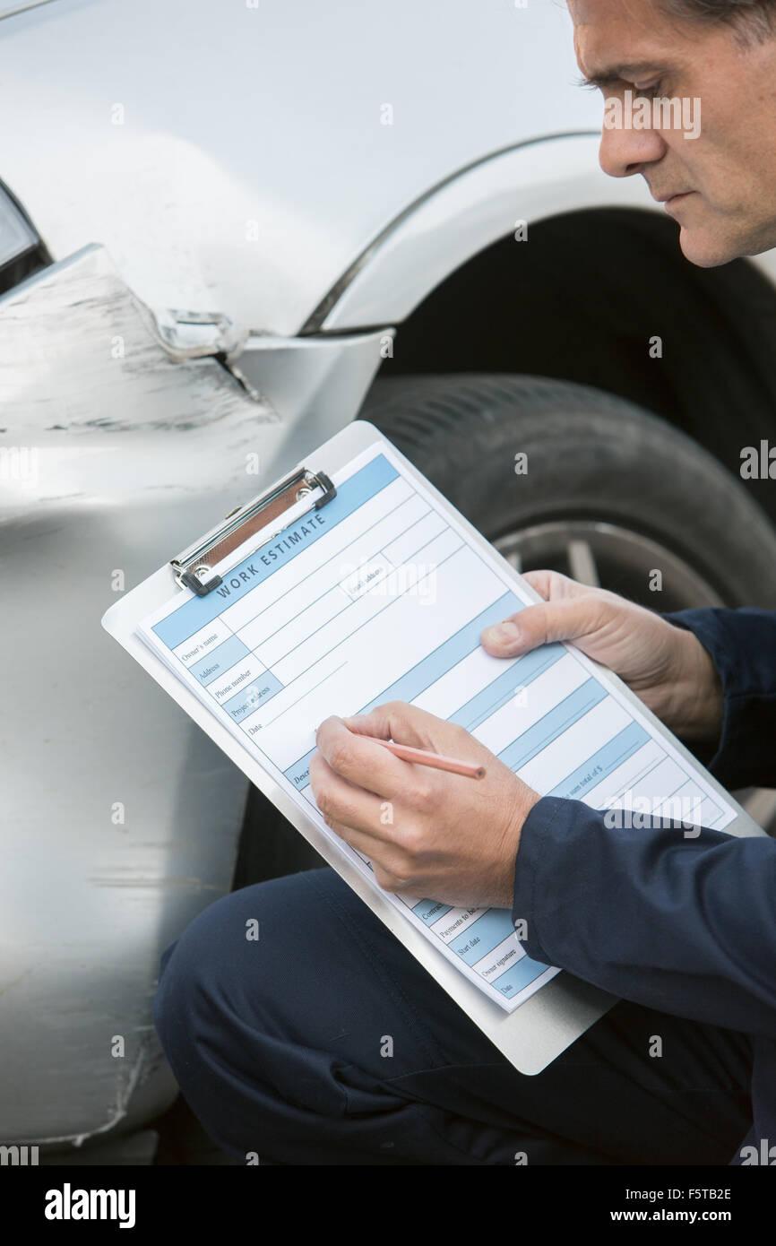 Automechaniker Workshop Inspektion Schäden an Fahrzeug und Reparatur Kostenvoranschlag ausfüllen Stockbild