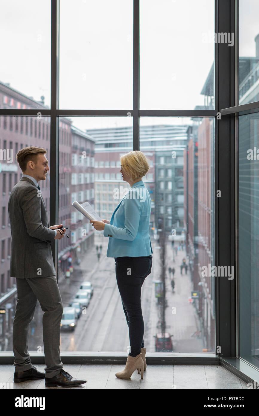 Finnland, Helsinki, Geschäftsleute diskutieren Projekt durch Fenster Stockbild