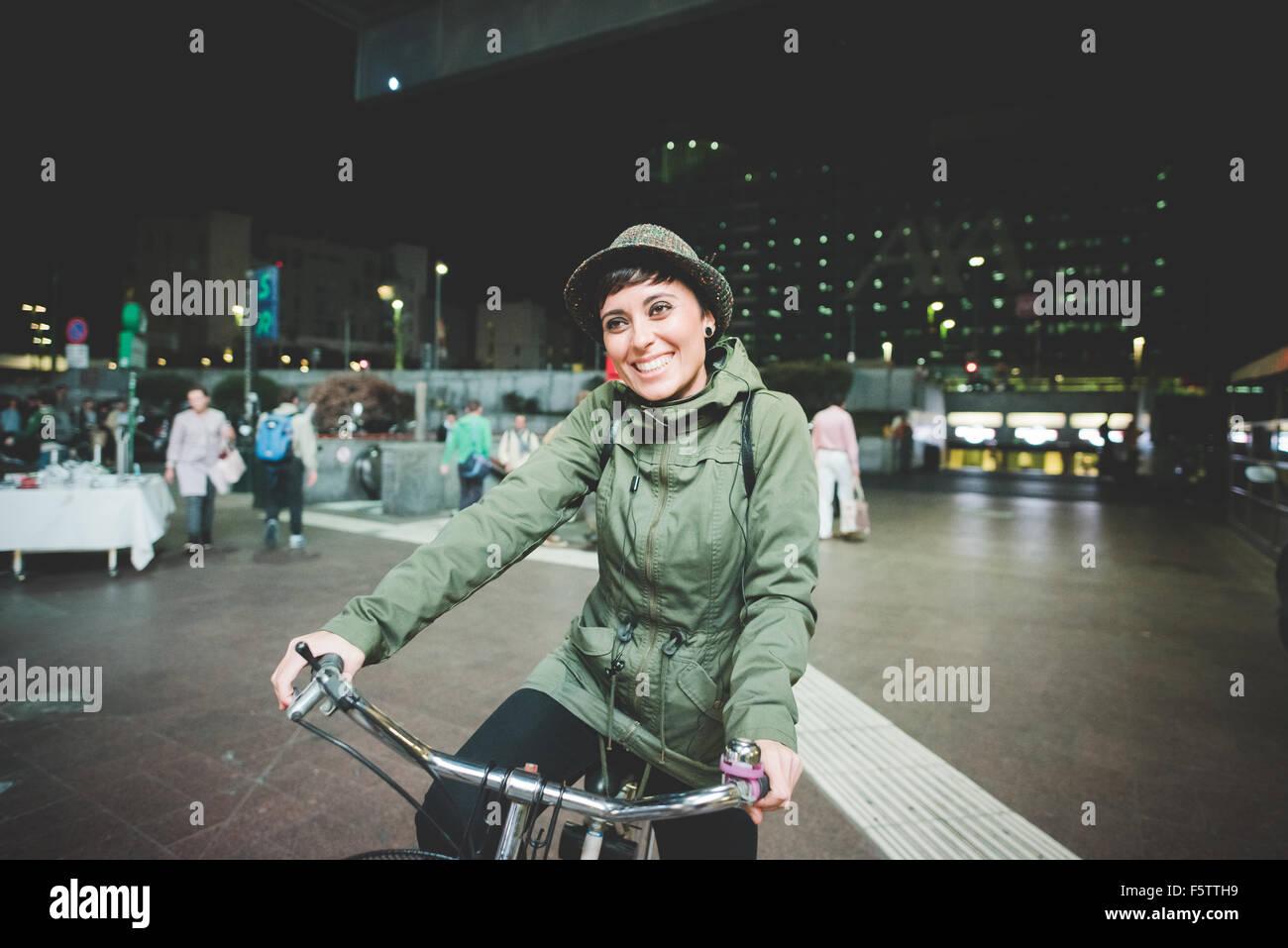 Halbe Länge des jungen schönen kaukasischen braun glattes Haar Frau Fahrrad fahren in der Nacht, mit Blick Stockbild