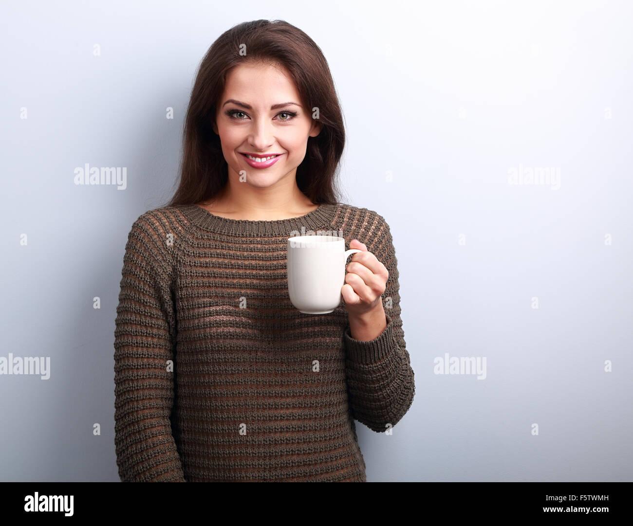 Lächelnde lässige junge Frau mit Tasse Tee suchen glücklich auf blauem Hintergrund Stockbild
