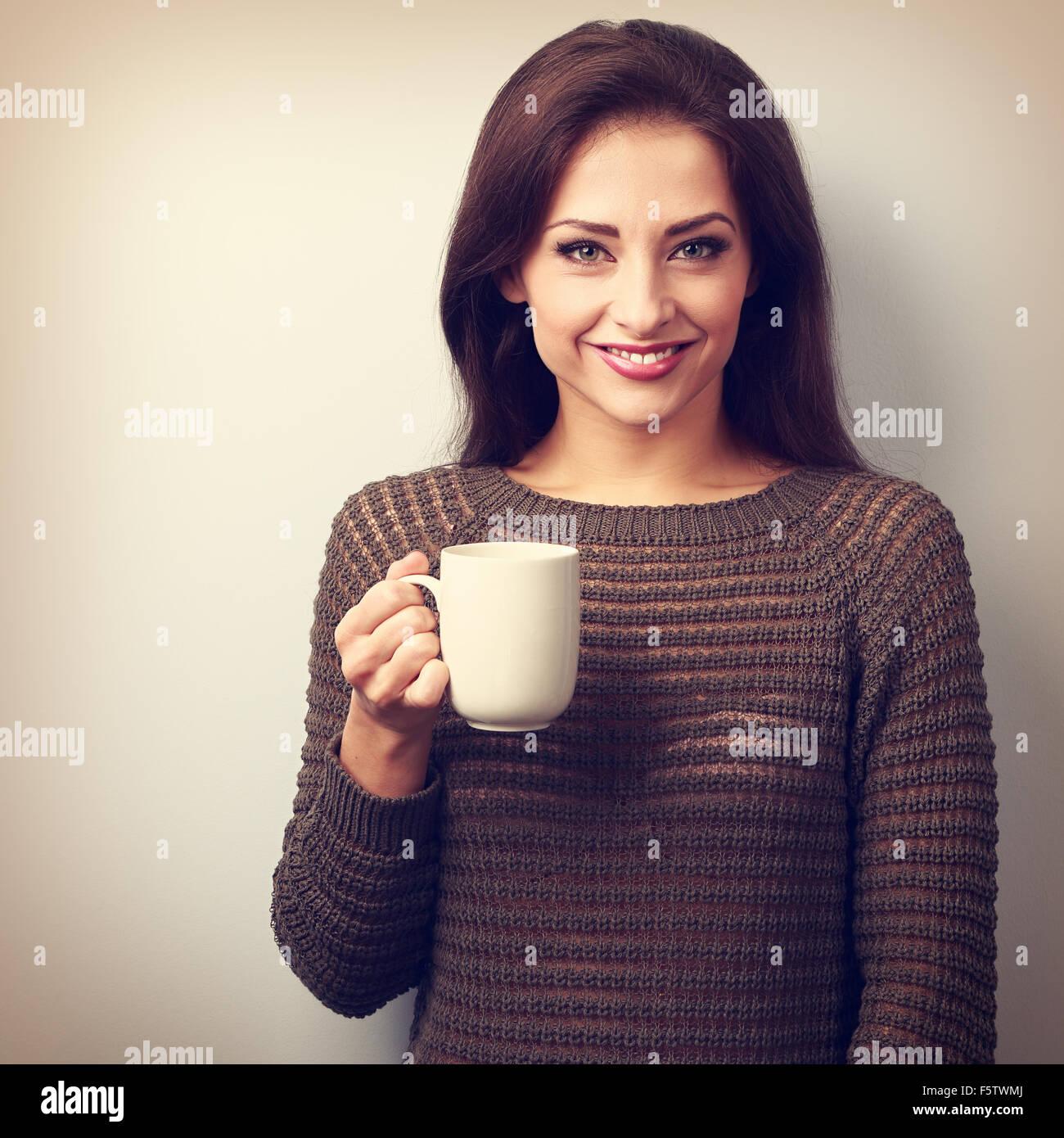 Lässige junge Frau mit Tasse Tee suchen glücklich lächelnd. Vintage Porträt Stockbild