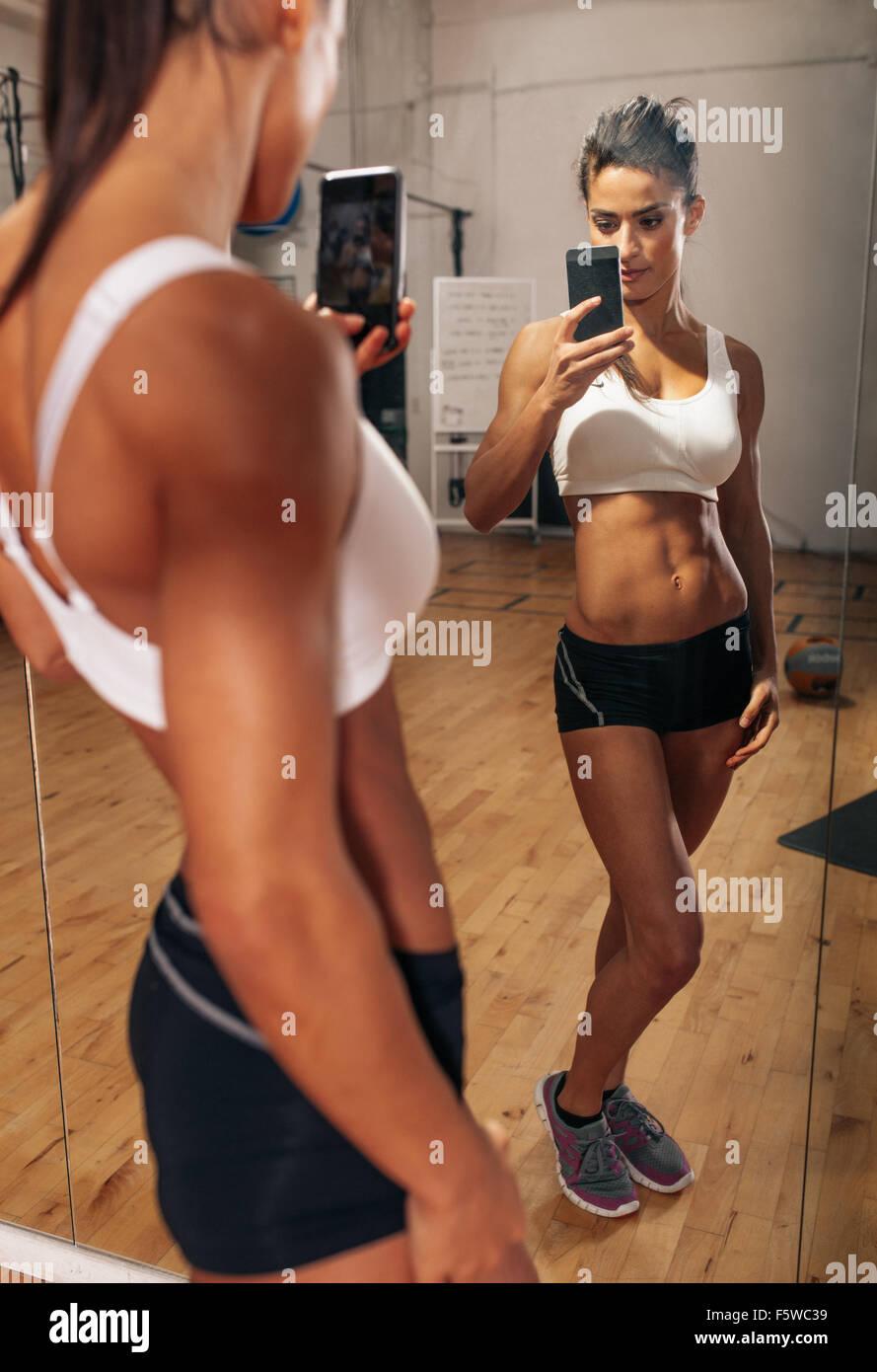 Fitness-Modell, wobei ein Selbstporträt aus der Reflexion im Spiegel mit ihrem Mobiltelefon. Muskulöse Stockbild