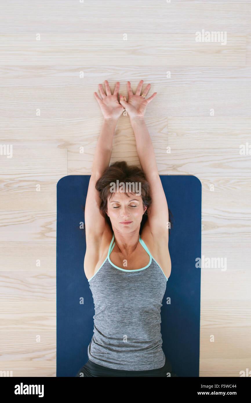 Draufsicht der Frau am Boden liegend, mit ihren Augen geschlossen und Arme gestreckt. Fitness-Frau Ausübung Stockbild