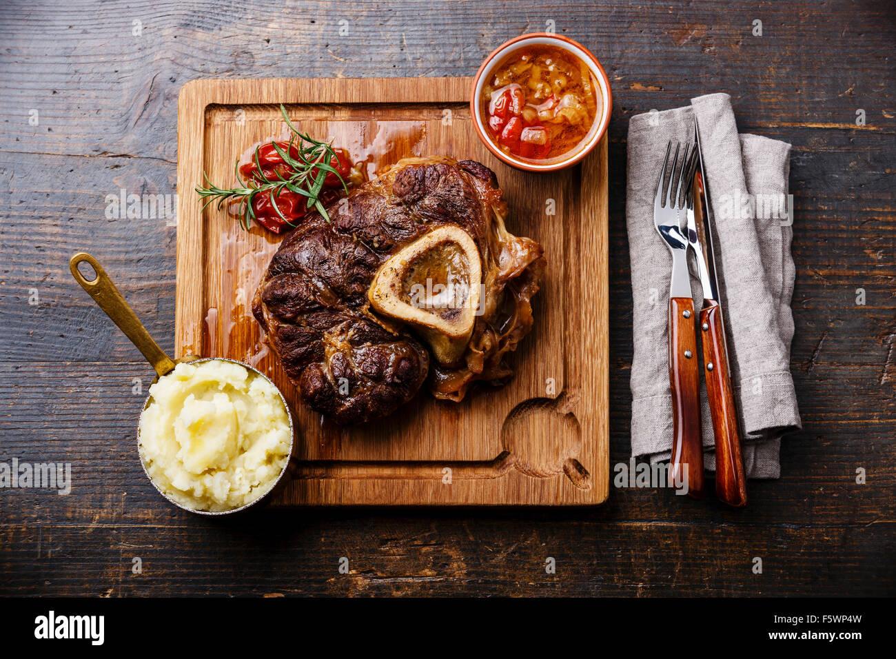 Ossobuco Kalbshaxe mit Tomaten und Kartoffelpüree auf dem Board auf hölzernen Hintergrund vorbereitet Stockbild