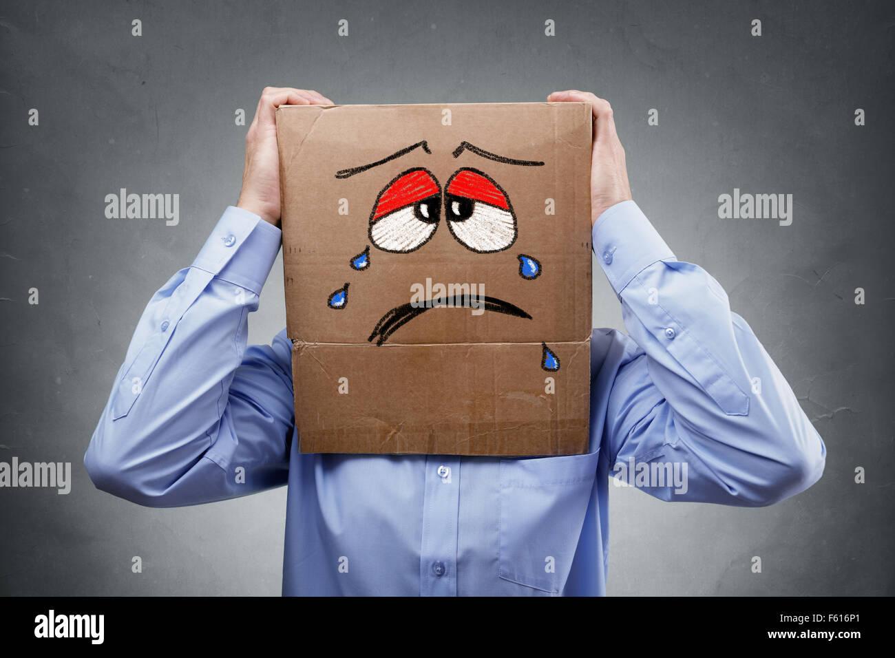 Mann mit Karton auf dem Kopf zeigt traurigen Ausdruck Stockbild