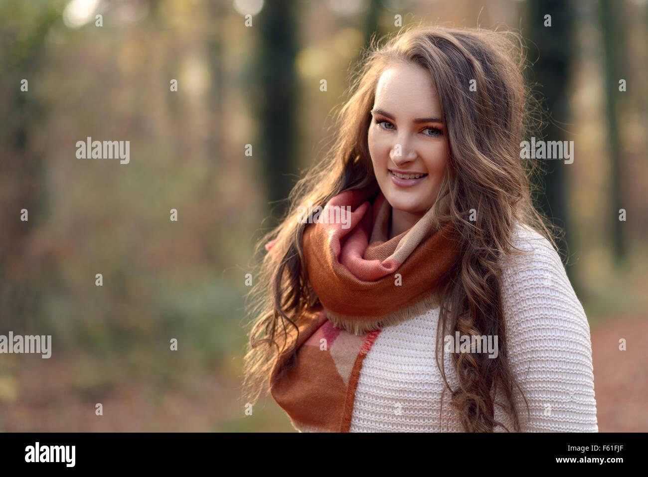 Sehr modische junge Frau im Freien in einem herbstlichen Wald trägt einen schicken Schal über ihr Trikot Stockbild
