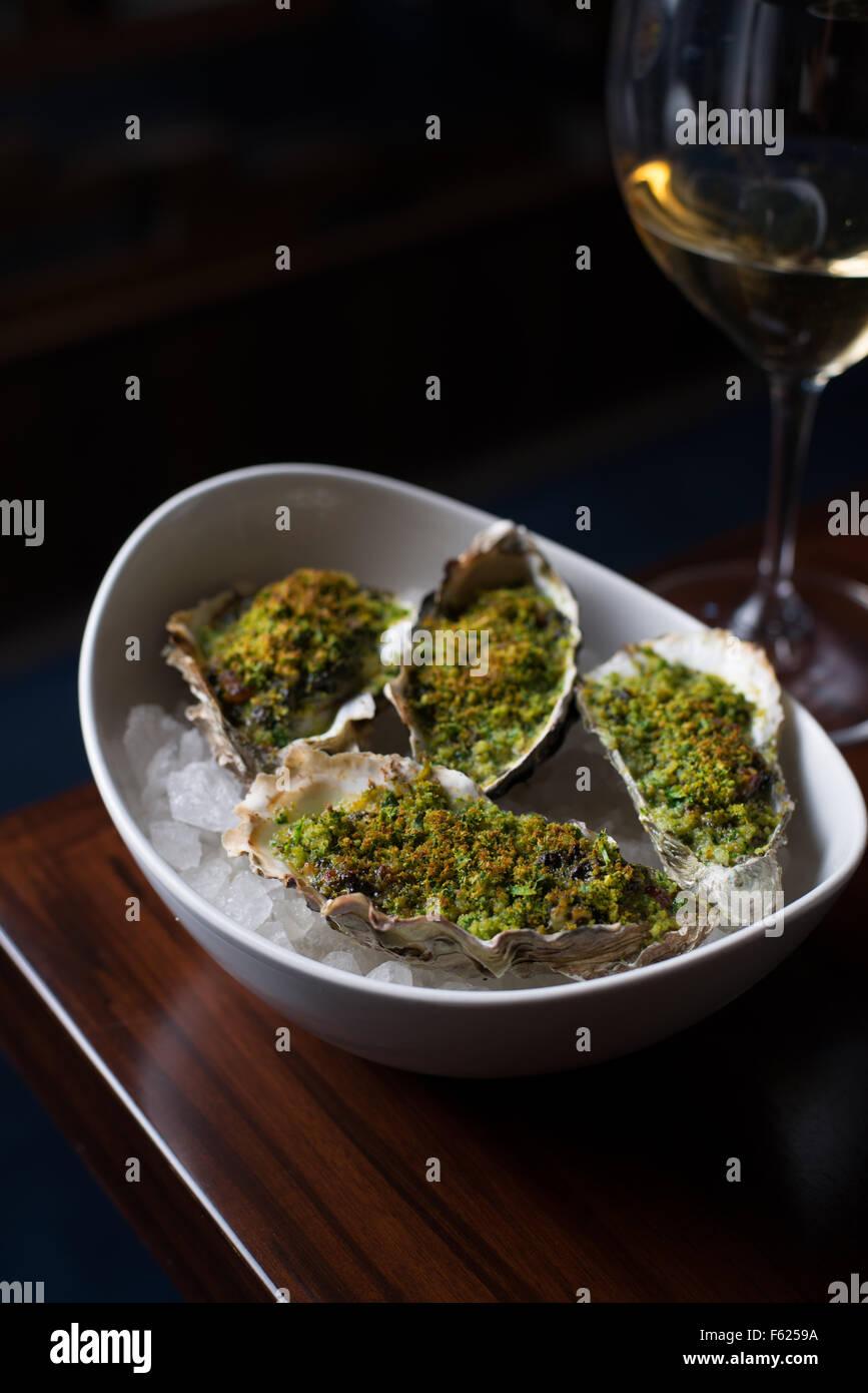 Seitlicher Blick auf Rockefeller Austern auf Eis an der Ecke einer Tabelle mit einem Glas Weißwein im Hintergrund. Stockbild