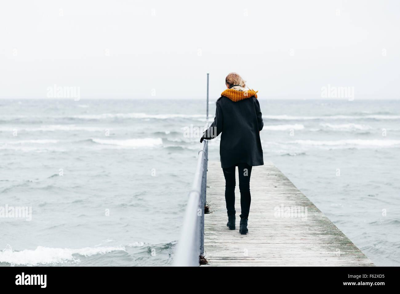 Voller Länge Rückansicht der Frau zu Fuß auf Pier über Meer Stockbild