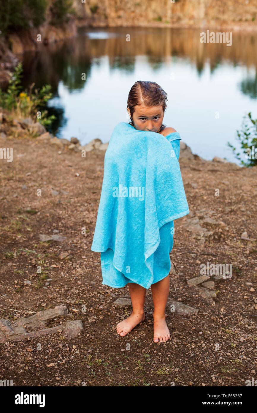 In voller Länge Portrait von Mädchen gewickelt im Handtuch stehen am Seeufer Stockbild