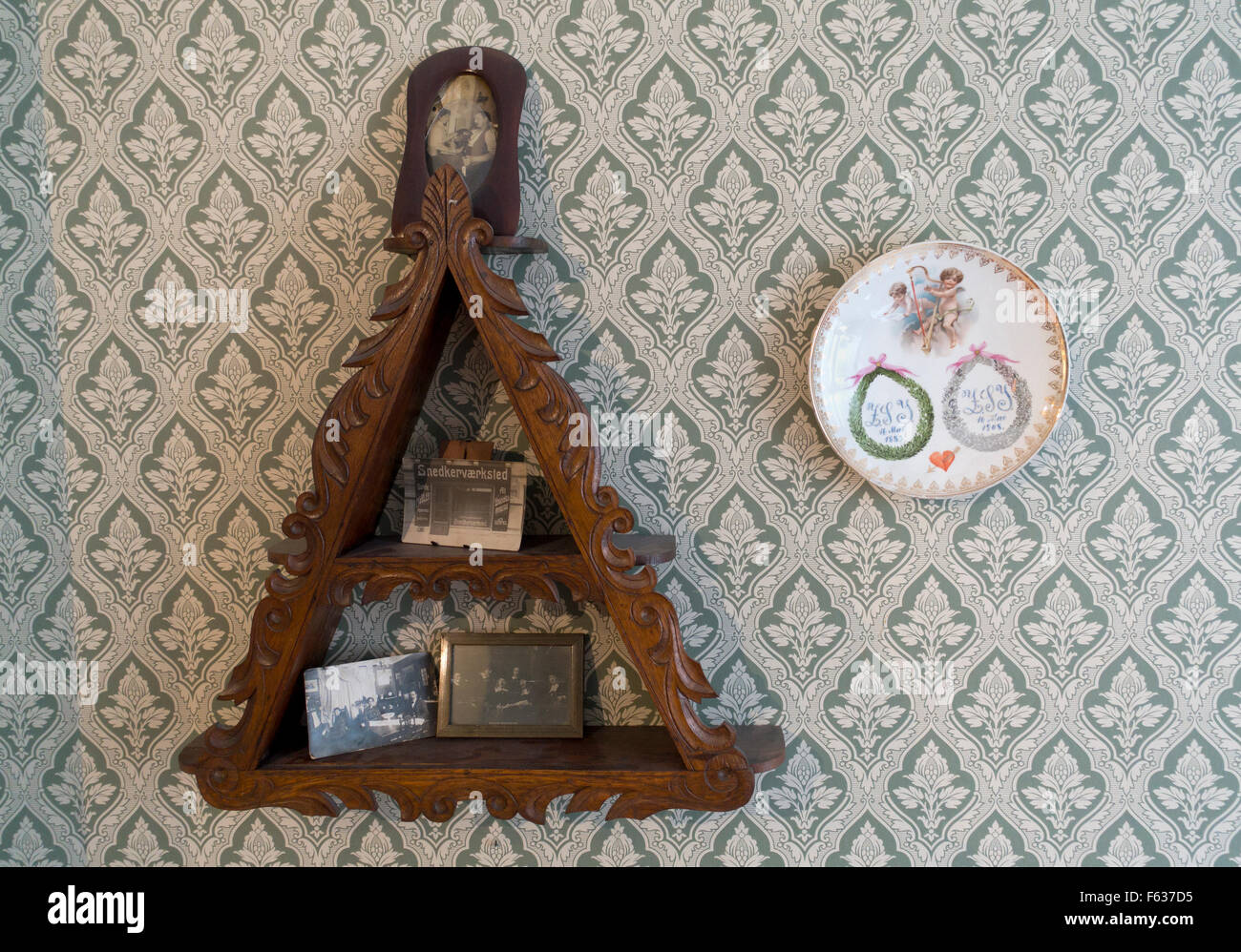 Alten dreieckige Regal mit Familie und kleinen Tischler Geschäftsfotos neben einer Silberhochzeit-Plakette. Stockbild