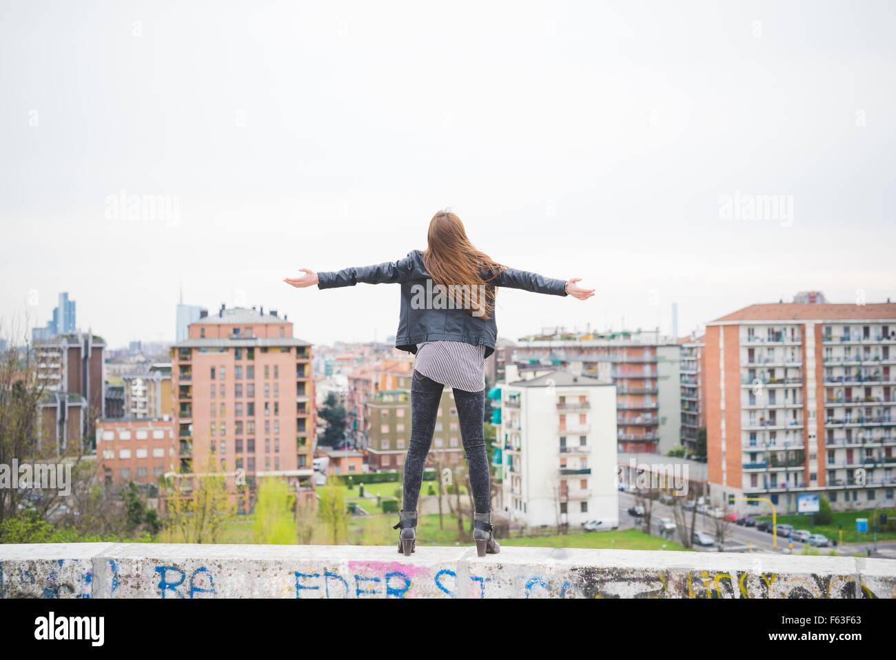 Junge schöne kaukasischen blonde Mädchen mit Armen weit offen in den Vororten steht auf einer kleinen Stockbild