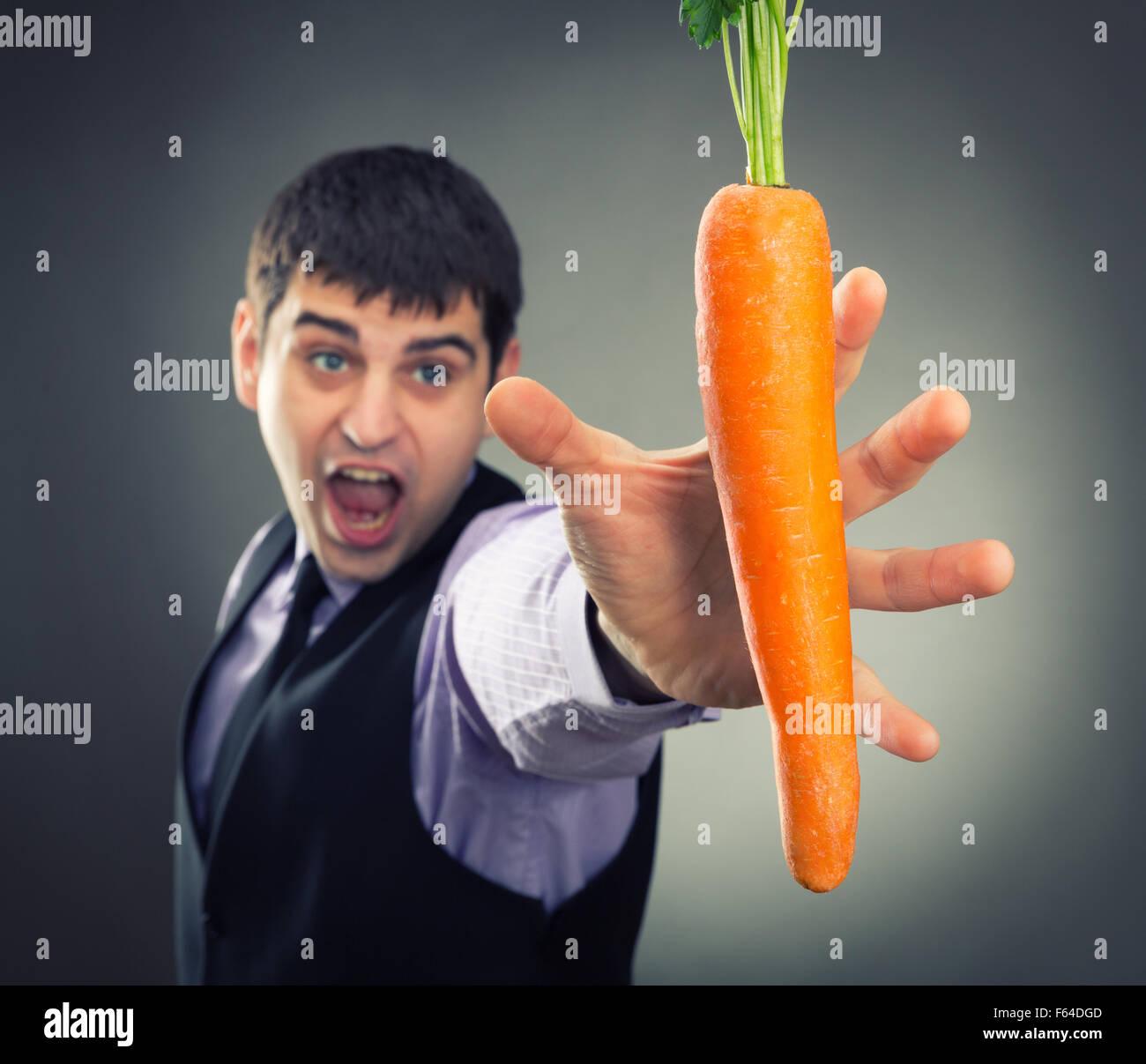 Mann, der versucht, frischen Karotten zu erreichen Stockbild