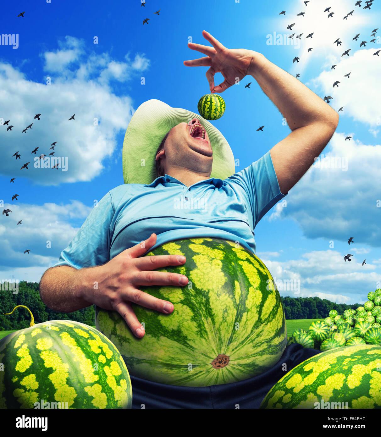 Bizarre Bauer mit Wassermelone statt den Bauch auf Feld im Sommer Stockbild