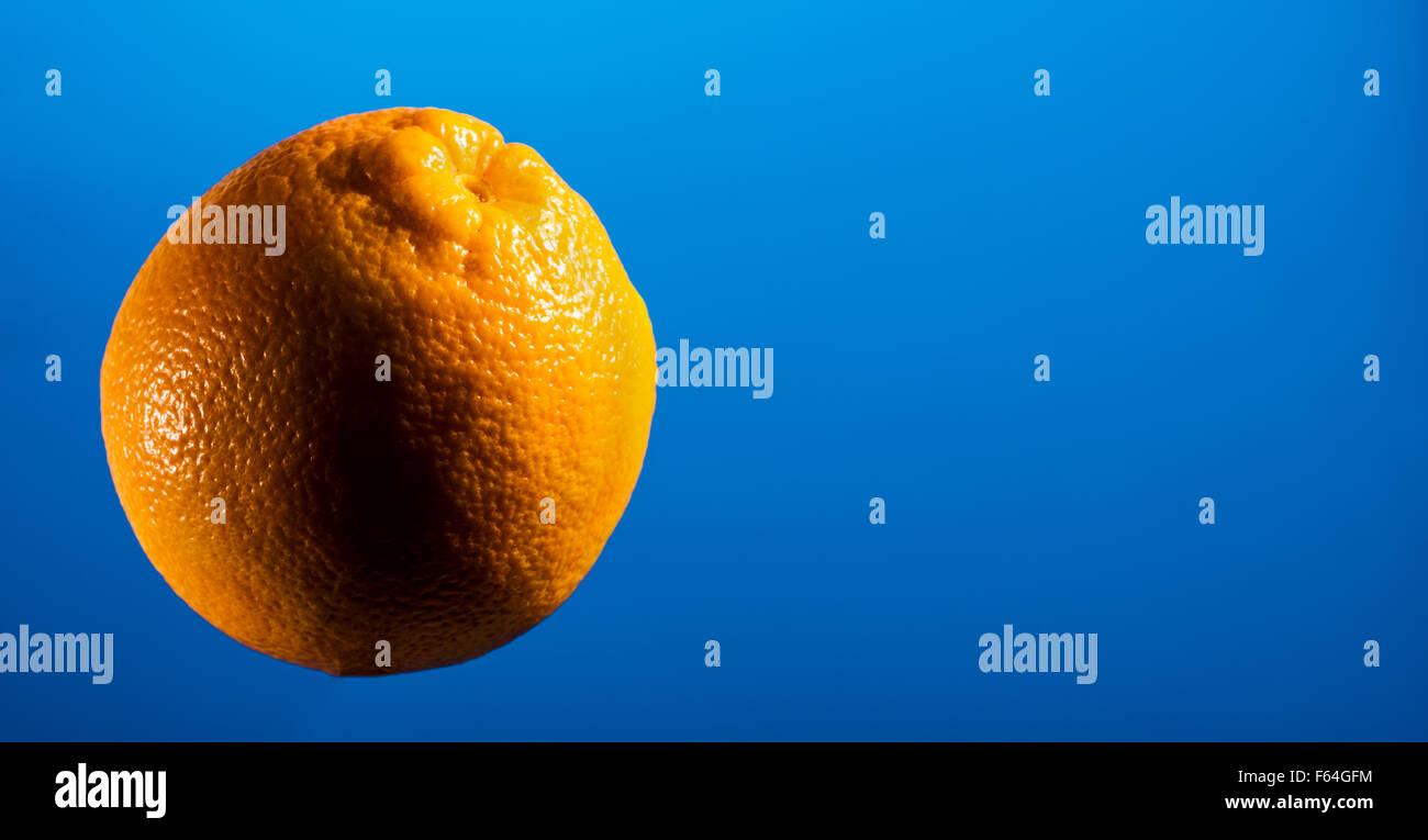ORANGE auf blauem Hintergrund, Raum für Textlayout, Exemplar, Text, Schriftart, Obst, Lebensmittel, Vitamin Stockbild