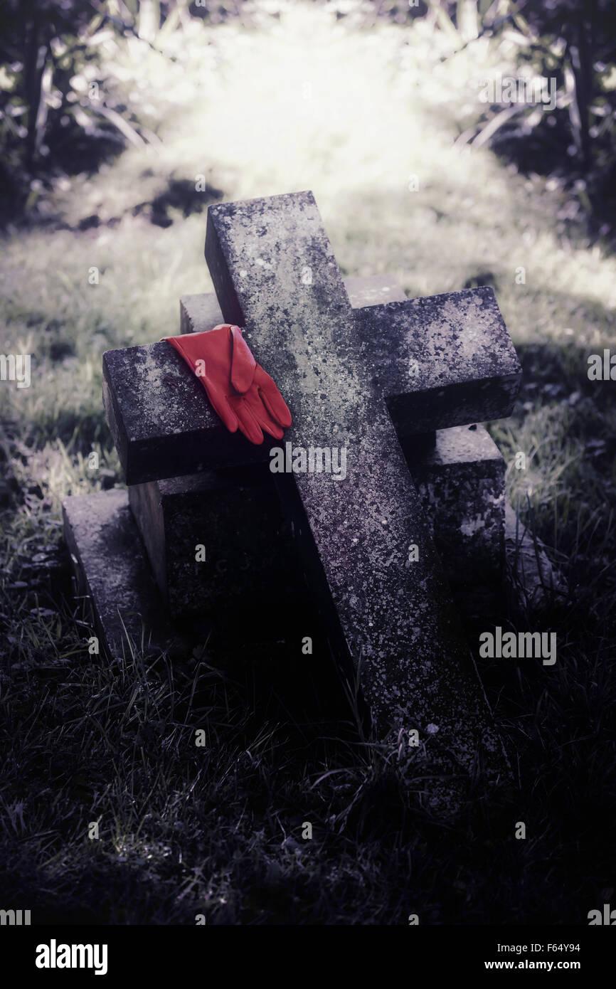 einen roten Handschuh auf einem Grab Stockbild