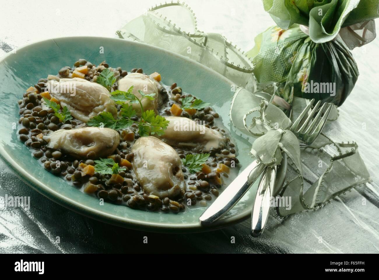 Warme Austern mit cremigen Linsen Stockfoto
