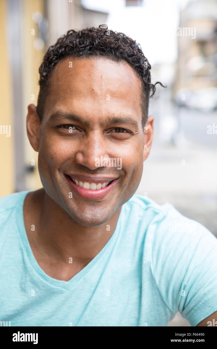 Kopfschuss von jeder ethnischen Mann lächelnd, mit einem leichten blau grün T-shirt. Stockbild