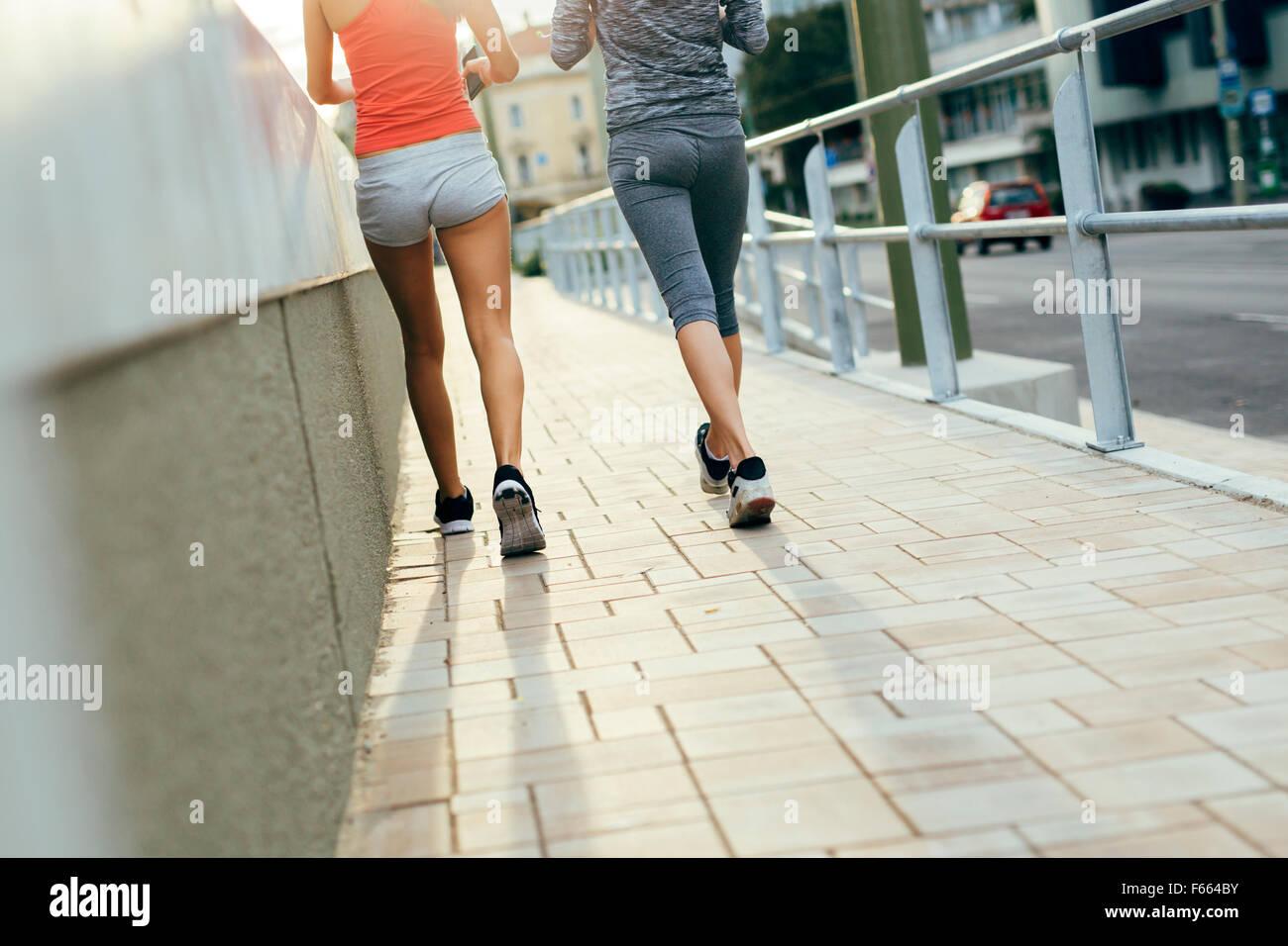 Zwei Frauen, die durch Joggen in der Stadt, während die Sonne untergeht Stockbild