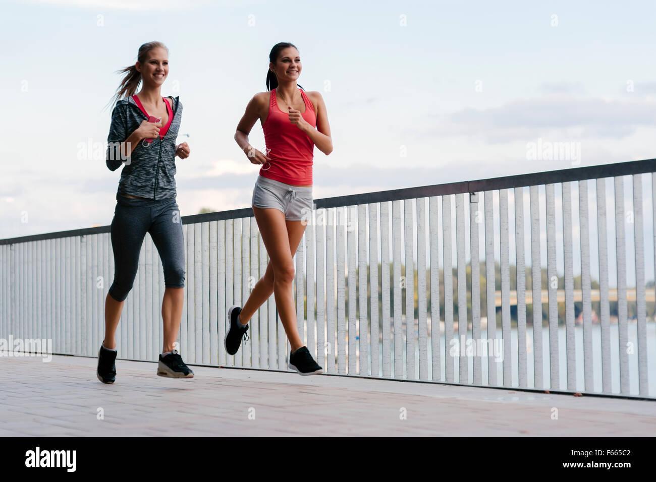 Zwei sportliche Frauen Joggen in der Stadt beim Musikhören Stockbild