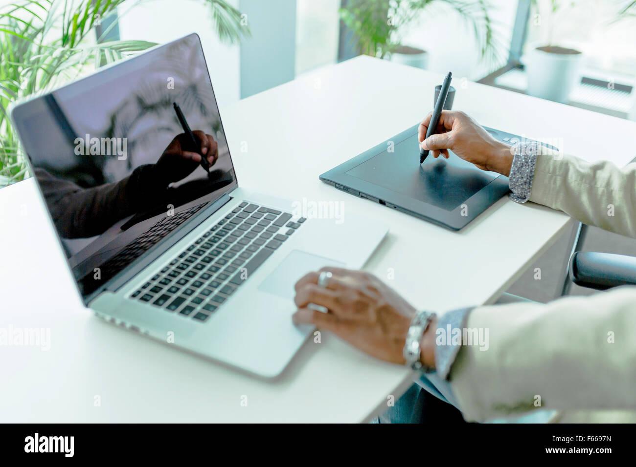 Grafikdesigner mit Digitizer mit seinen Überlegungen auf dem Notebook Bildschirm anzeigen Stockbild