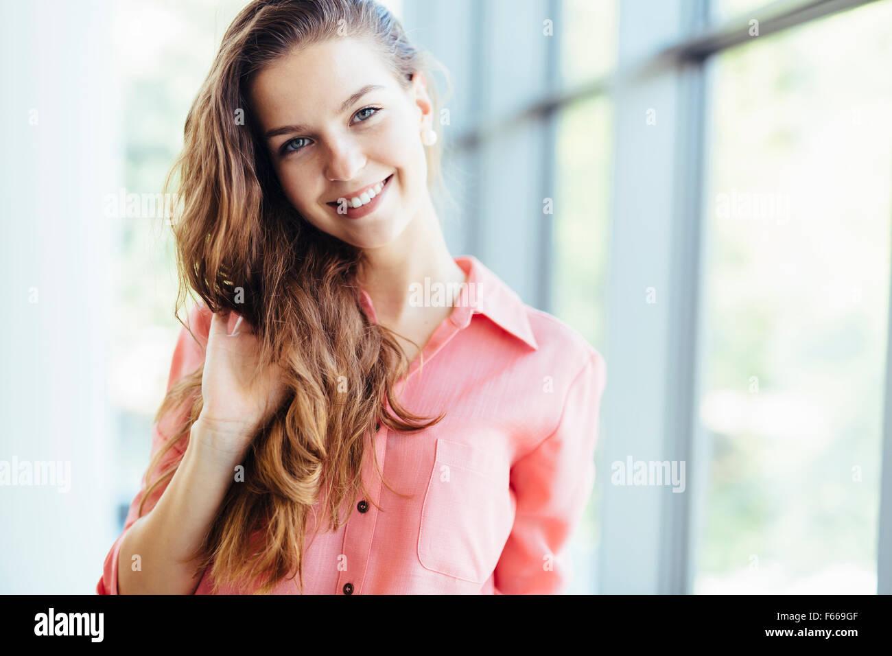 Schöne Geschäftsfrau hält ihr Haar und lächelt. Gefühl des wahren Glücks Stockbild
