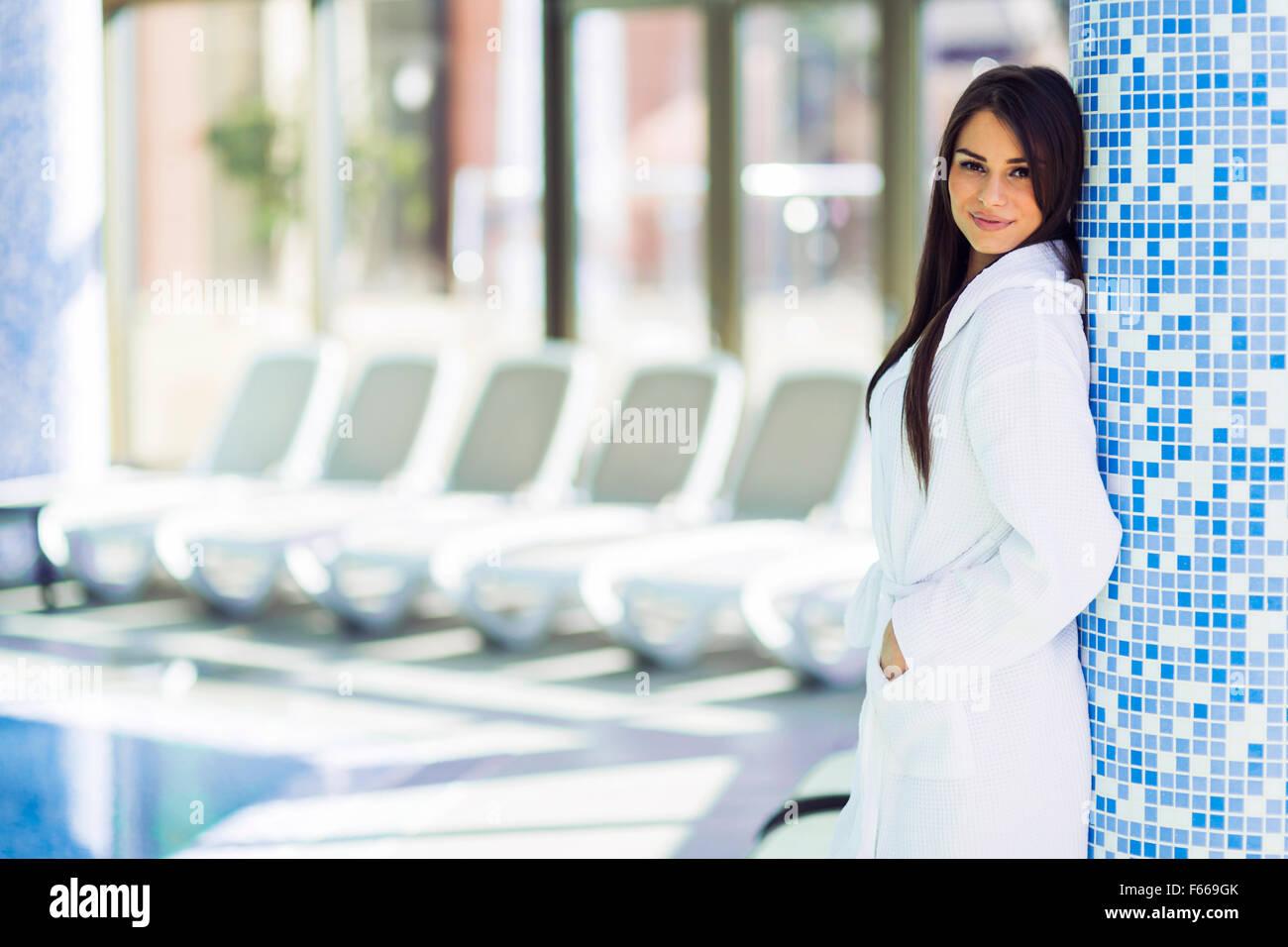 Porträt einer schönen jungen Frau im Bademantel neben einem Schwimmbad Stockbild