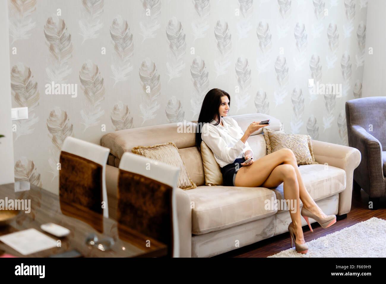 Schöne junge Frau mit Fernbedienung im Wohnzimmer und elegant gekleidet Stockbild