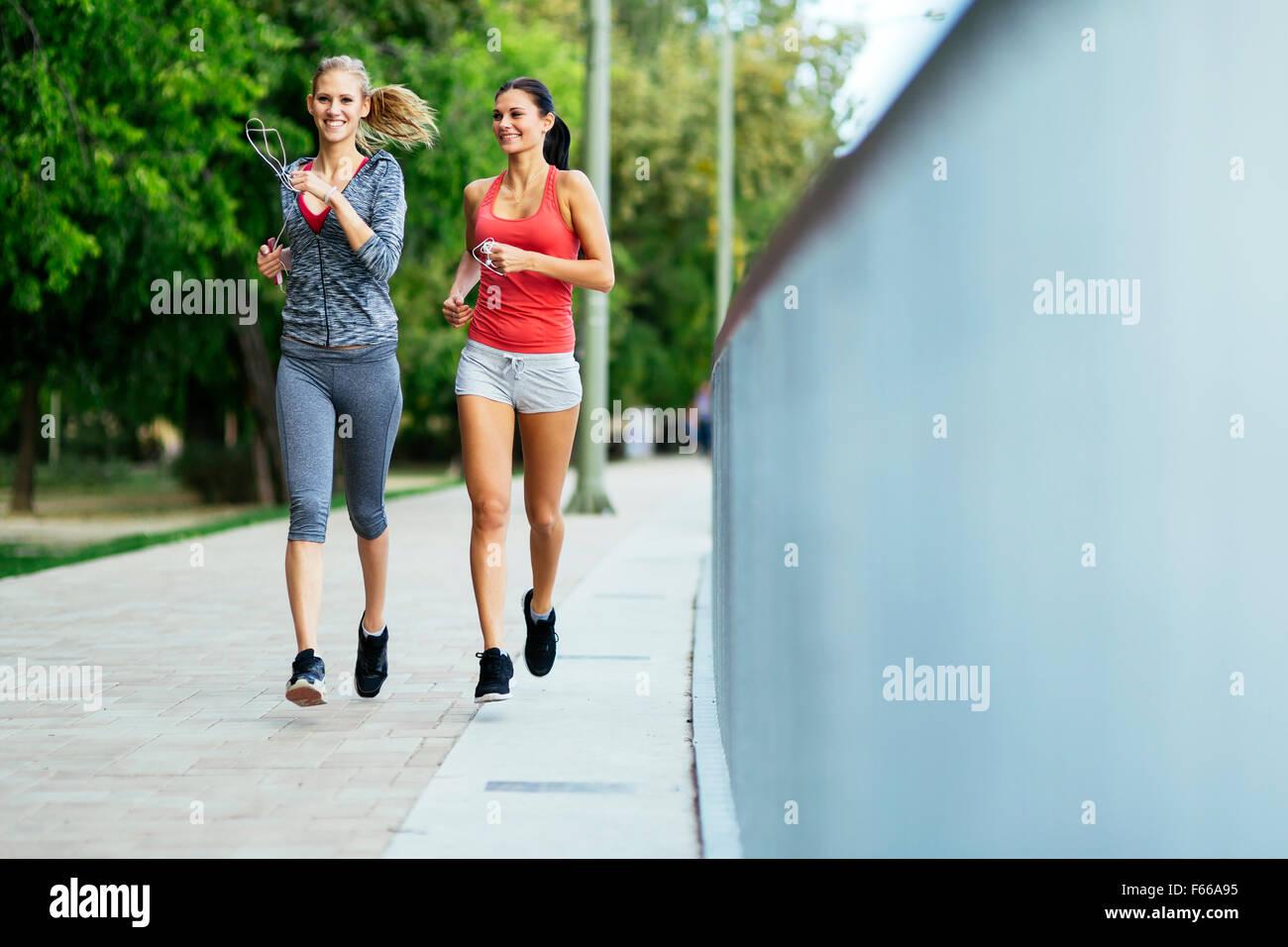 Zwei Frauen, die durch Joggen in Stadt Stockbild
