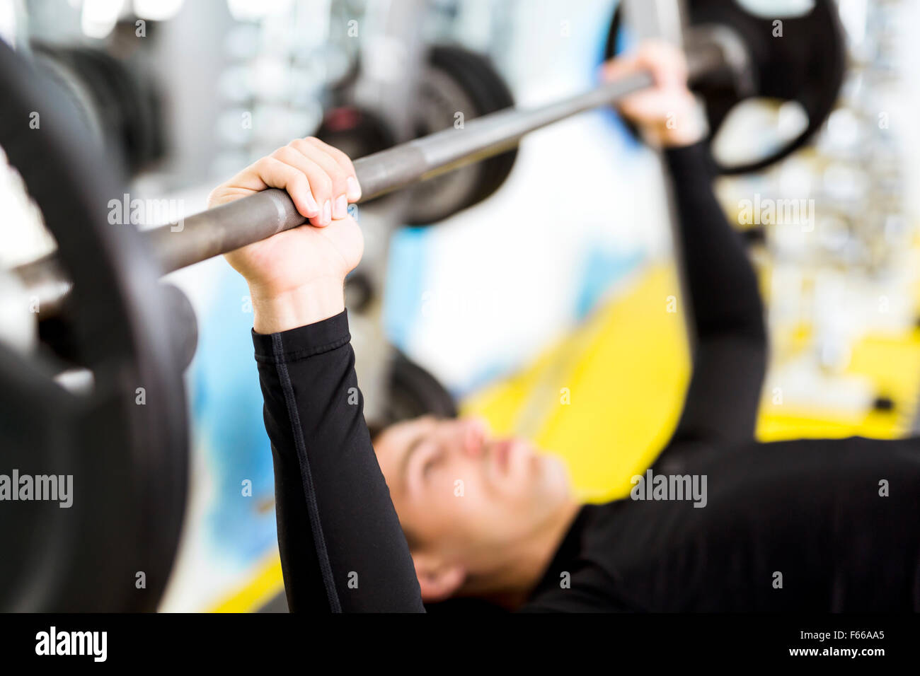 Nahaufnahme von jungen hübschen männlichen Übungen auf beim Bankdrücken Stockbild