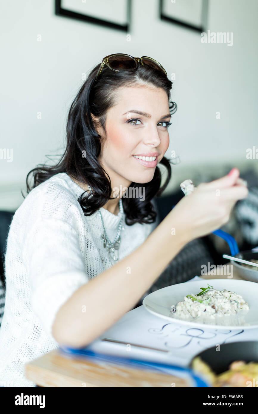 Schöne junge Dame mit einem Essen in einem Restaurant und im Begriff, einen Bissen zu nehmen Stockbild