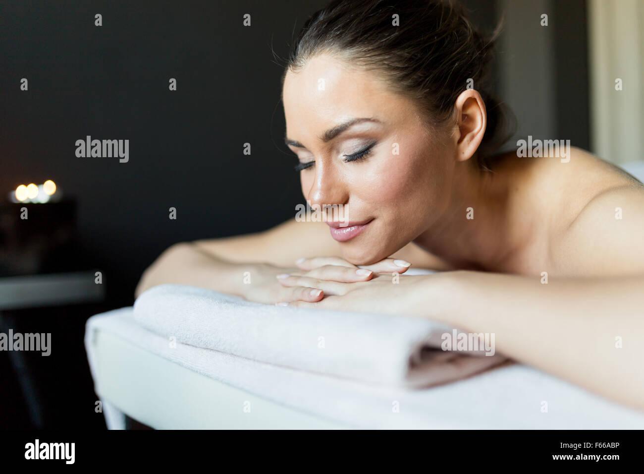 Porträt einer jungen und schönen Frau mit geschlossenen Augen auf einer Massageliege in einem dunklen Stockbild