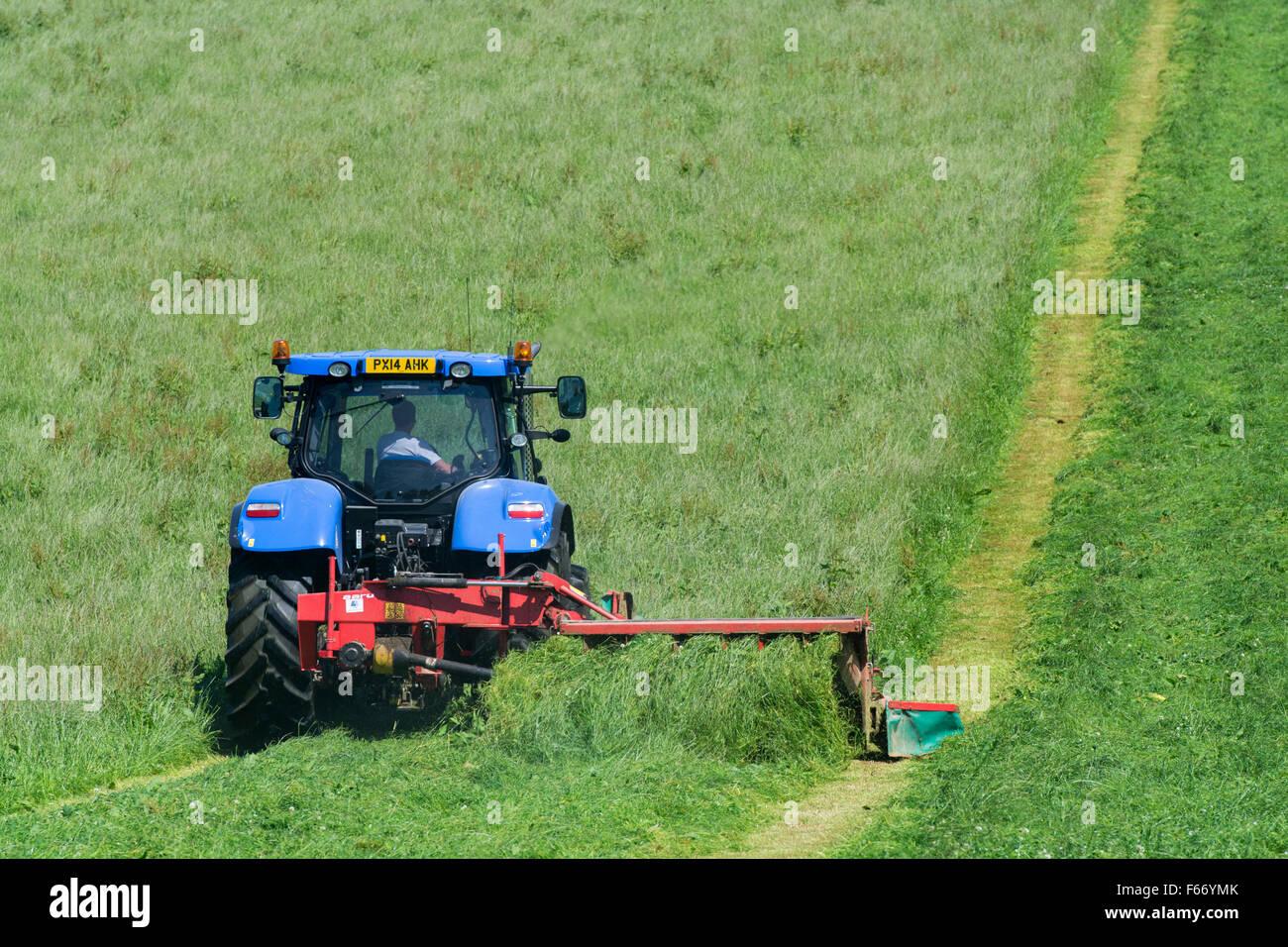 Mähen einer Wiese mit einem New Holland T7 Traktor mit Kvernland Front- und Seitenairbags Mähaufbereiter Stockbild