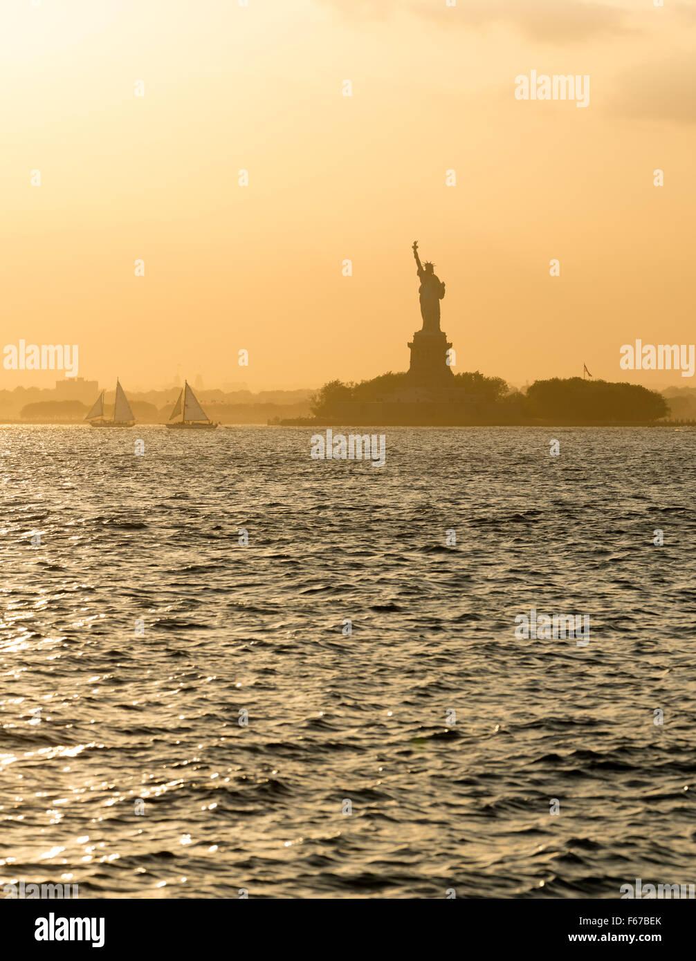 Freiheitsstatue vor Sonnenuntergang im dunstigen New Yorker Hafen Stockbild