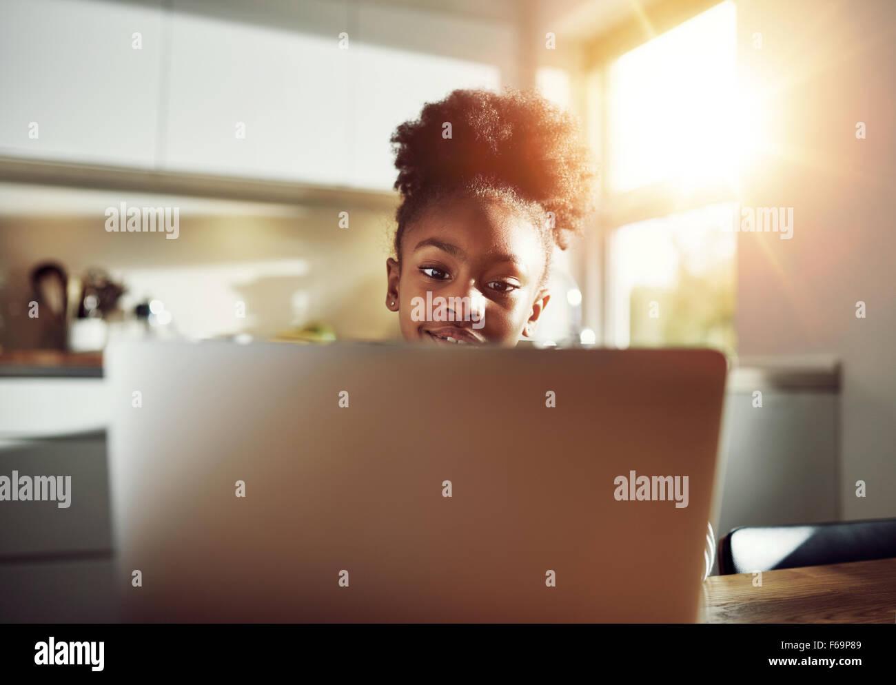 Lächelnd schwarze Mädchen mit einem netten Frisur sitzt an einem Laptop im Internet surfen und Ihre Social Stockbild