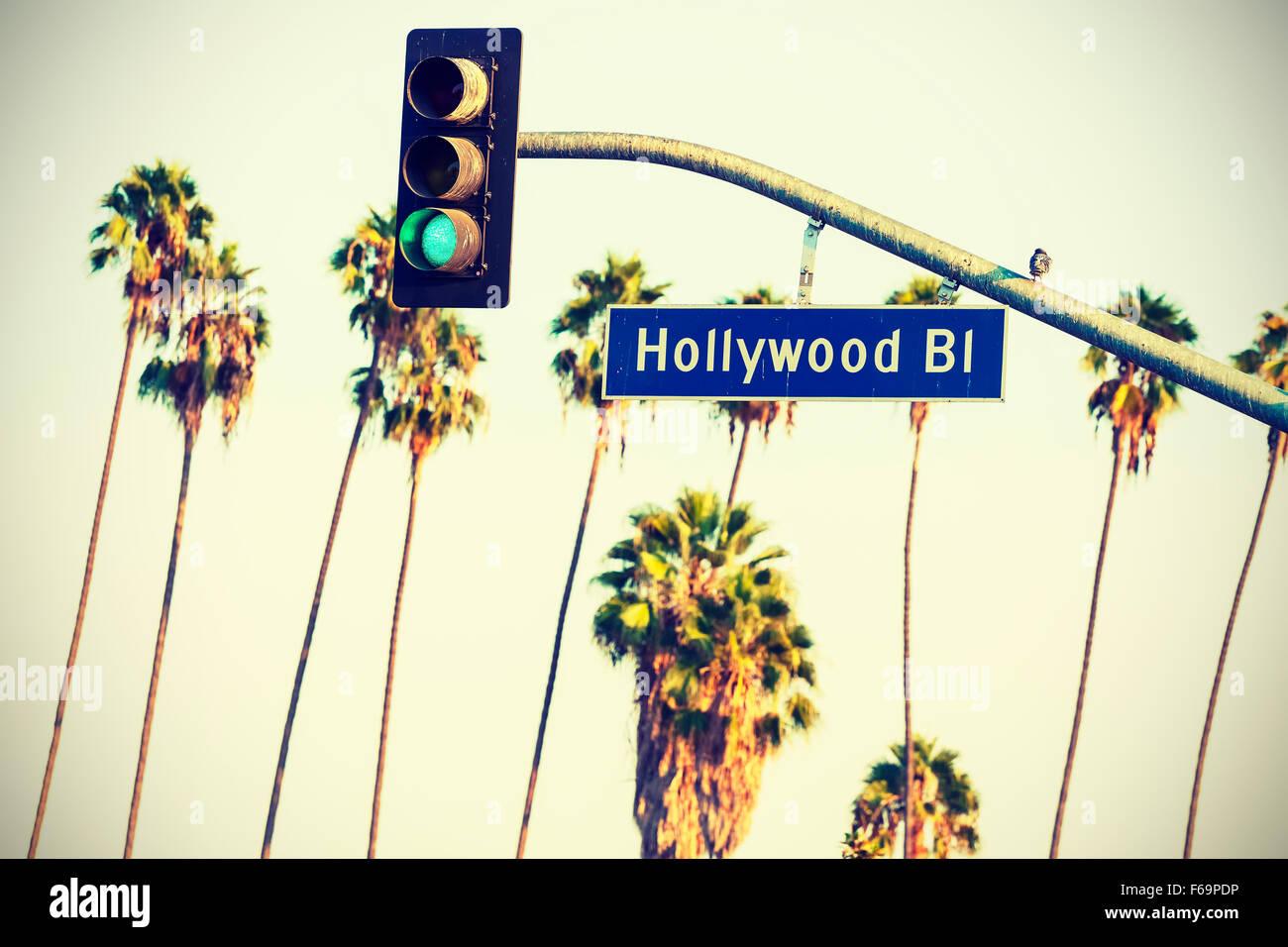 Überqueren Sie verarbeitete Hollywood Boulevard-Schild und Ampeln mit Palmen im Hintergrund, Los Angeles, USA. Stockbild