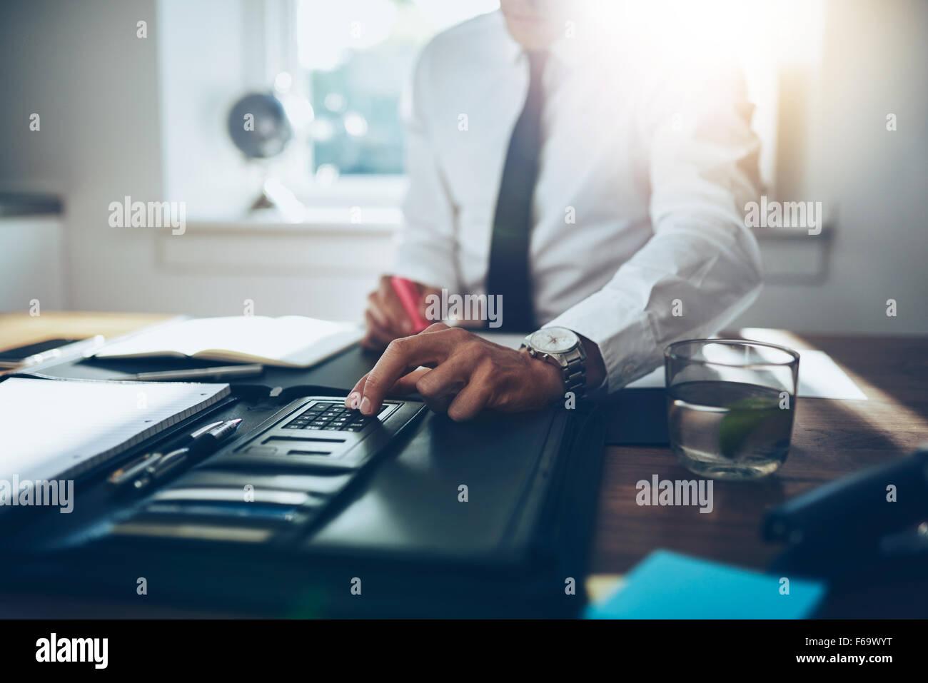 in der Nähe Konten, Business Mann oder Rechtsanwalt Steuerberater arbeiten auf Verwendung eines Taschenrechners Stockbild