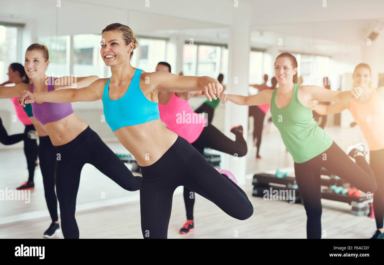 Junge Frauen in bunten Sportbekleidung Training im Aerobic-Kurs in der Turnhalle mit Fokus auf eine lächelnde Stockbild