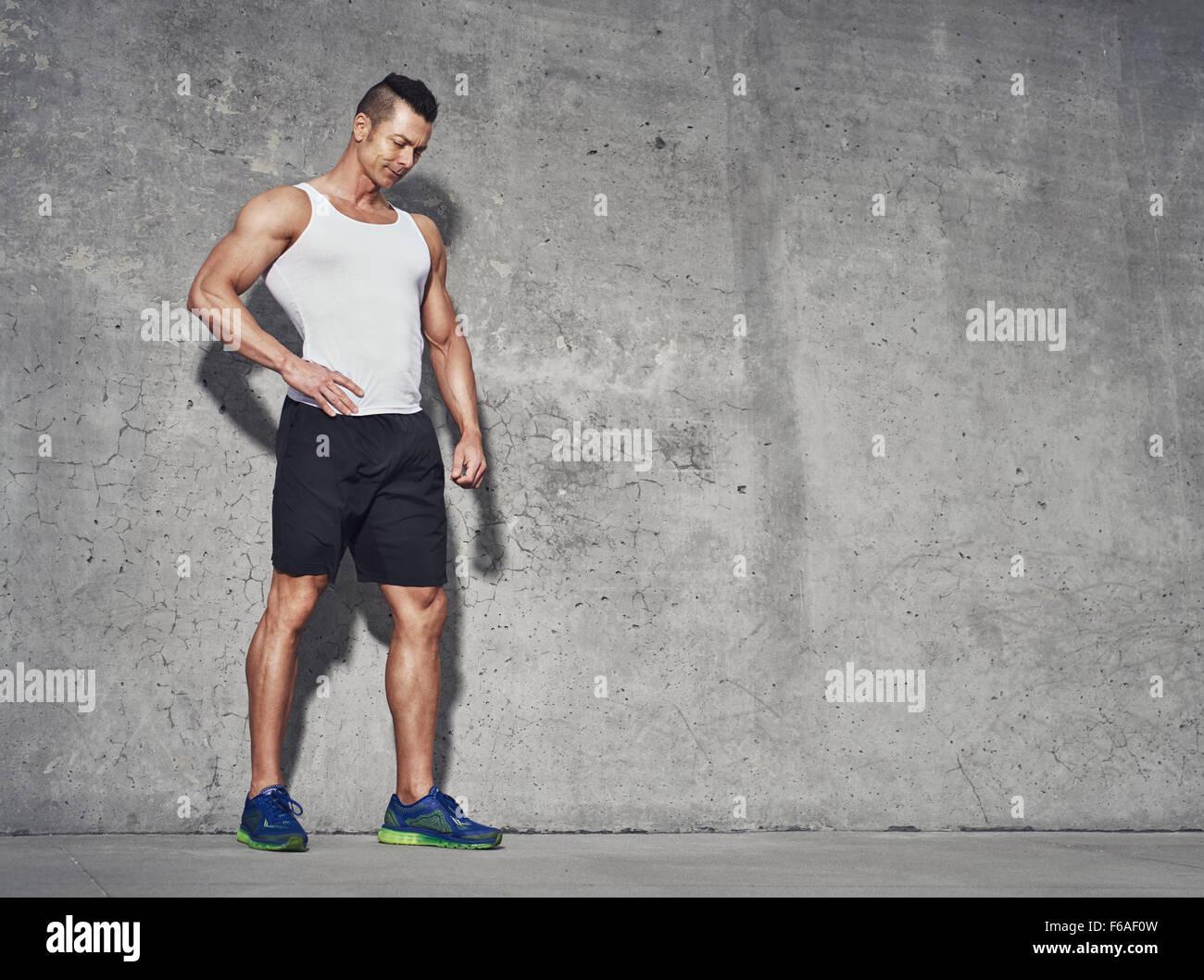 Männlichen Fitness-Modell in weißen Tank-Top Entspannung nach dem Training. Grauer Hintergrund mit Platz Stockbild
