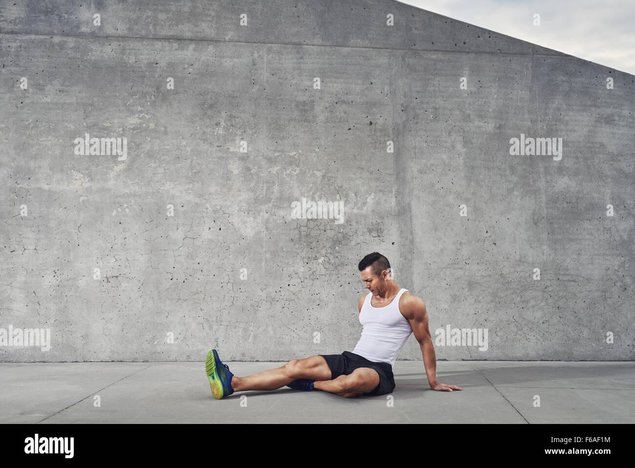 Fitness Sportler Menschen Entspannung und Stretching Muskeln und Beine tragen ein weißes Tank Top, gut gebaut, Stockbild