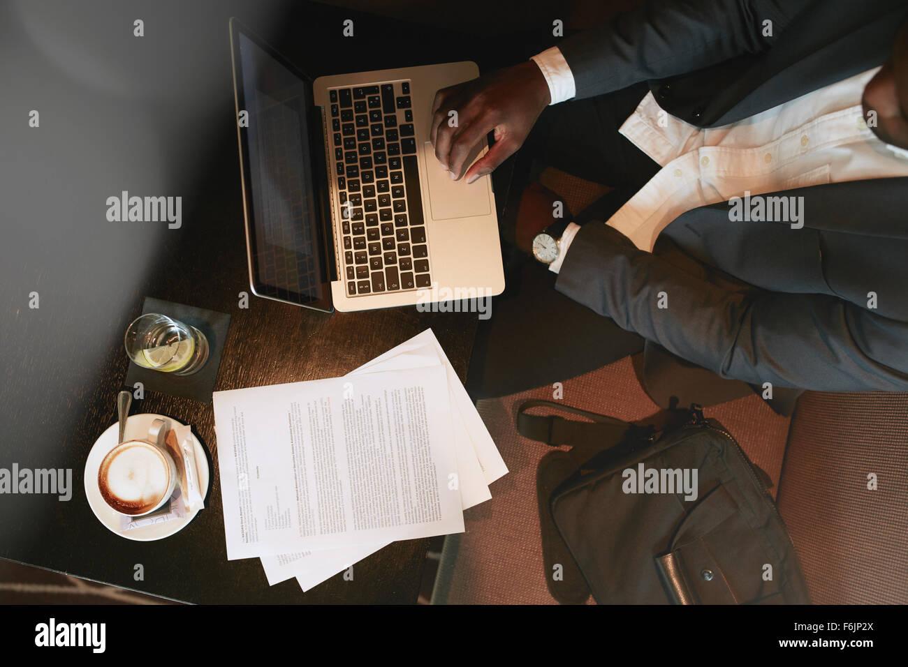 Draufsicht der Geschäftsmann sitzen im Café auf Laptop-Computer arbeiten. Kaffee, Wasser und Dokumente Stockbild