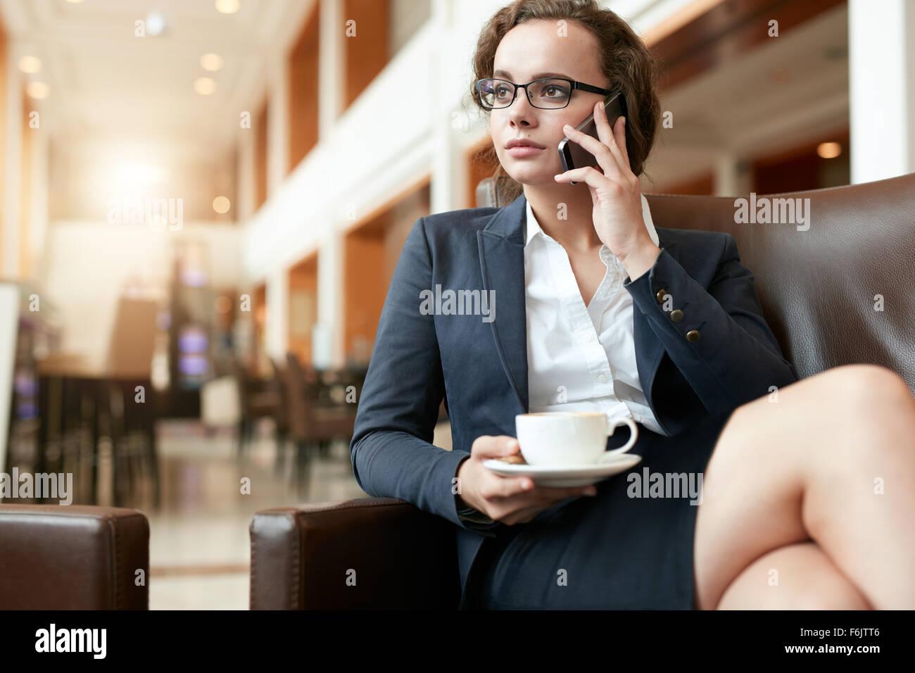 Porträt der Geschäftsfrau im Coffee Shop mit Handy sitzen. Weibliche Führungskraft mit Tasse Kaffee Stockbild