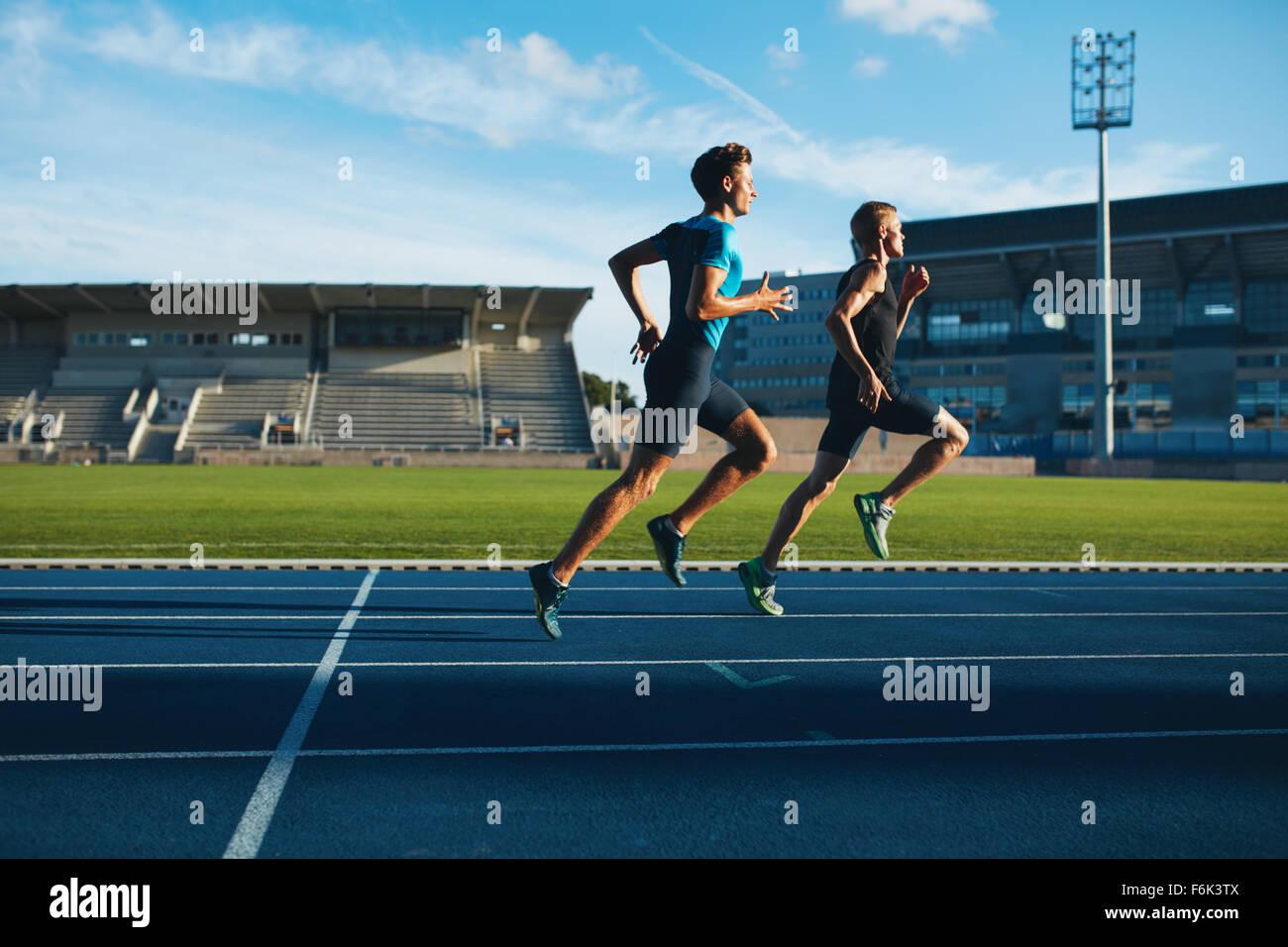 Zwei junge Männer, die auf der Rennstrecke. Männliche Profi-Athleten laufen auf Leichtathletik Rennen verfolgen. Stockfoto