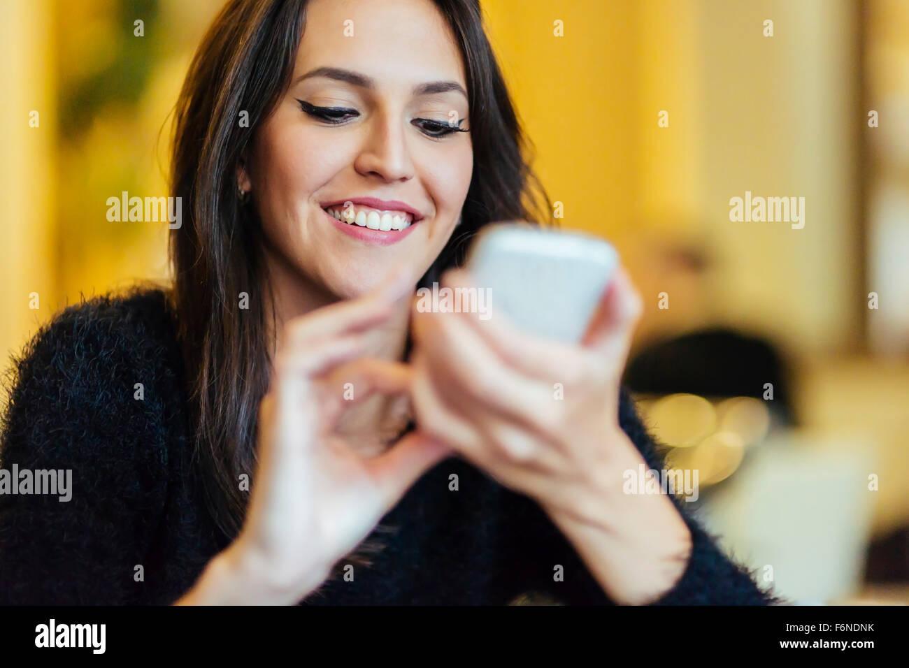 Schöne Brünette mit Smartphone Stockbild