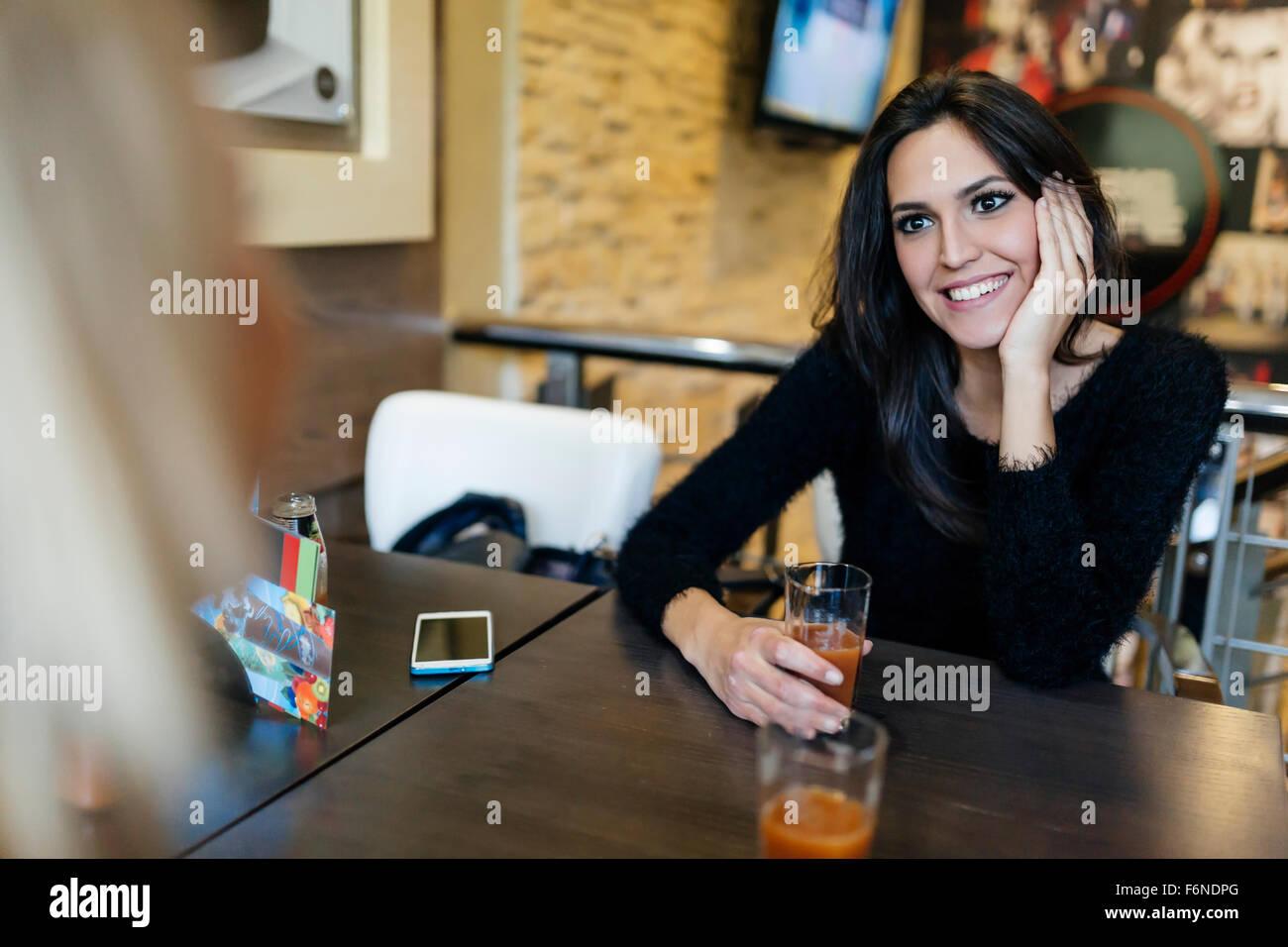 Schöne Brünette verbringt Zeit mit Freund im Café und lächelnd Stockbild