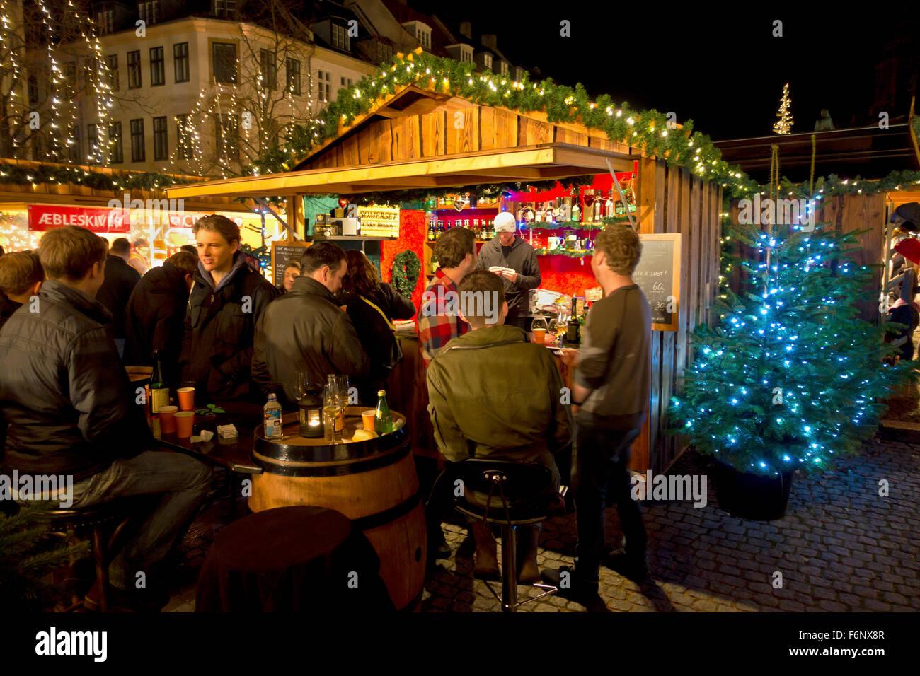 Junge Menschen haben ein Getränk auf dem Weihnachtsmarkt in Højbro Plads (Hoejbro Platz) auf der Strøget auf einem Stockfoto