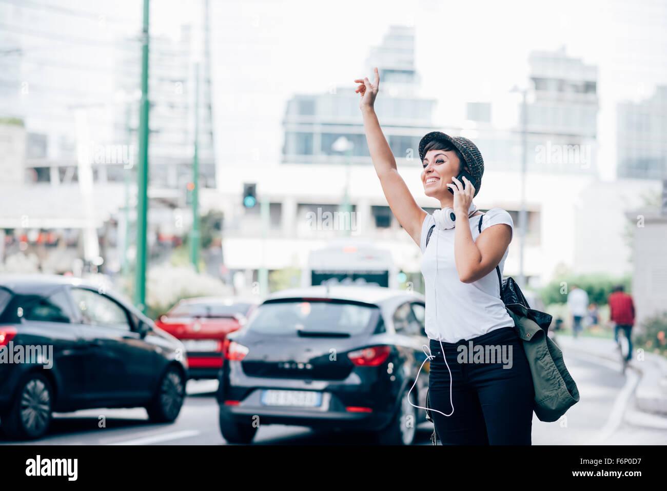 Knie Figur junge hübsche kaukasischen braun glattes Haar Frau fragt nach einem Taxi, hob die Arme beim Smartphone Stockbild